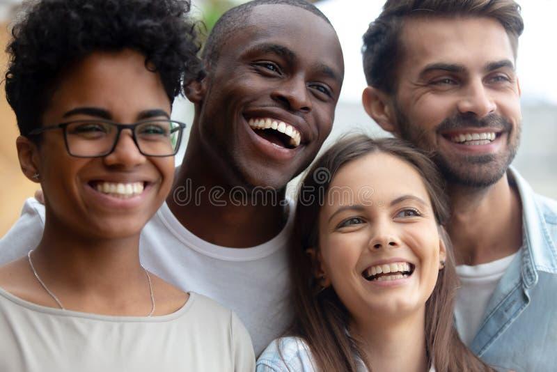 Rozochoceni multiracial szczęśliwi przyjaciele śmia się patrzeć daleko od pozujący dla fotografii zdjęcie stock