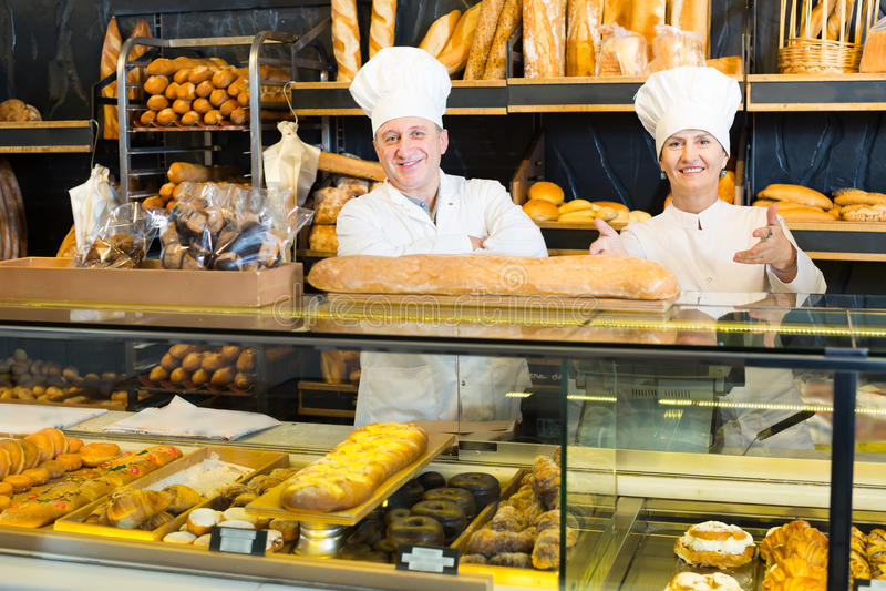 Rozochoceni piekarzi z świeżym chlebem w piekarni zdjęcia stock