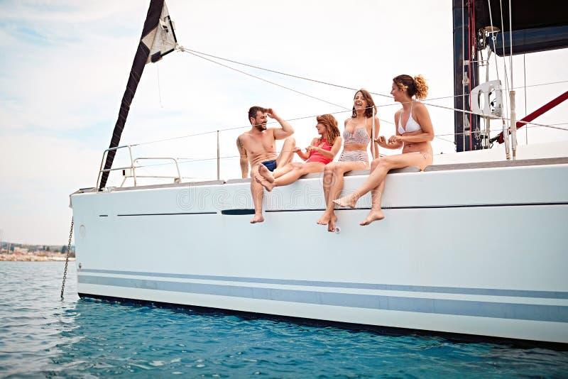 Rozochoceni przyjaciele podróżują na jachcie i mieć zabawie tw?j wakacje rodzinny szcz??liwy lato zdjęcia royalty free