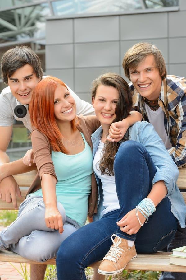 Rozochoceni przyjaciele wiszący szkoła wyższa kampusem out fotografia stock