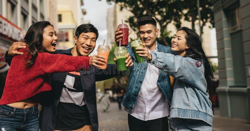 Rozochoceni przyjaciele wznosi toast napoje na ulicie zdjęcia royalty free