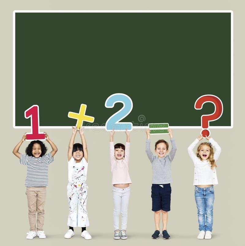 Rozochoceni różnorodni dzieciaki uczy się mathematics obraz stock