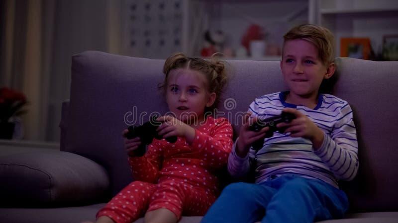 Rozochoceni rodzeństwa bawić się gra wideo używać konsolę przy nocą zamiast dosypiania obraz stock