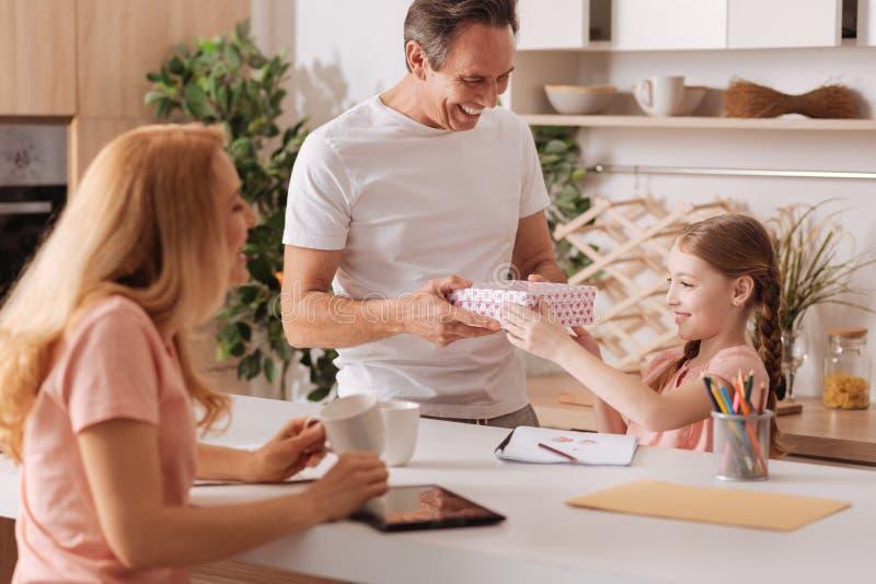 Rozochoceni rodzice gratuluje córki z wakacje w domu zdjęcia stock