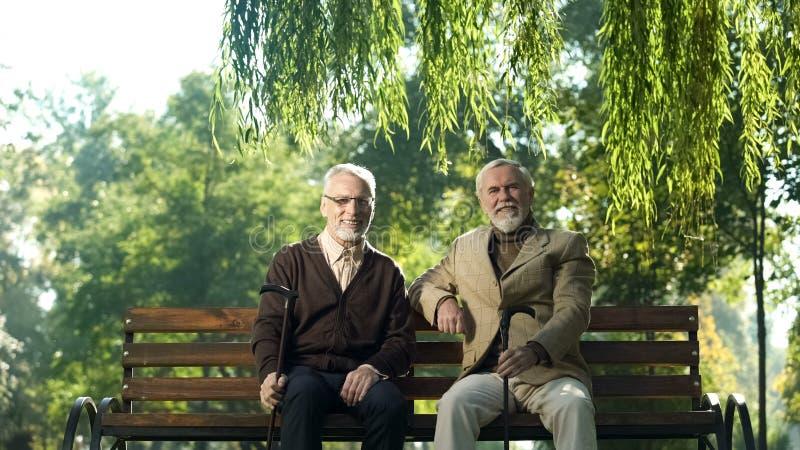 Rozochoceni starszy mężczyźni siedzi na ławce z chodzącymi kijami, szczęśliwy życie w starości zdjęcie royalty free