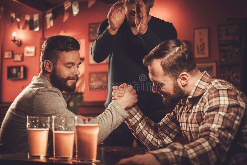 Rozochoceni starzy przyjaciele ma ręki zapaśnictwa wyzwanie w pubie zdjęcie royalty free