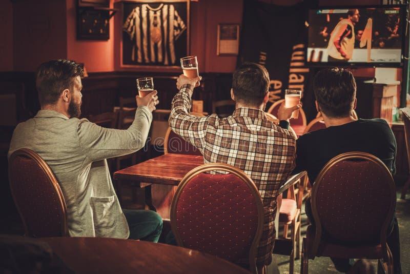 Rozochoceni starzy przyjaciele ogląda sporty i pije szkicu piwo w pubie zdjęcie stock