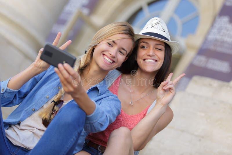 Rozochoceni turystyczni żeńscy przyjaciele bierze fotografie themselves fotografia stock