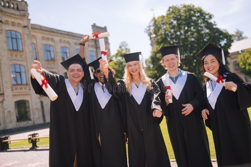 Rozochoceni ucznie świętuje ich skalowanie od uniwersyteta zdjęcia royalty free