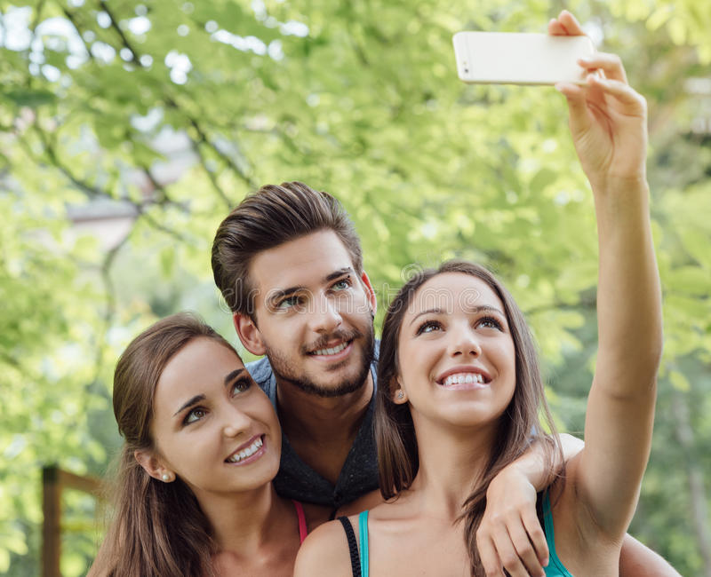 Rozochoceni wieki dojrzewania przy parkowymi bierze selfies fotografia royalty free