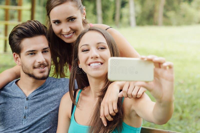 Rozochoceni wieki dojrzewania przy parkowymi bierze selfies fotografia stock