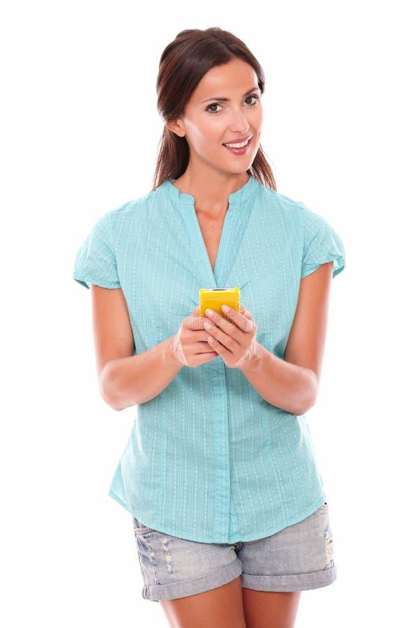 Rozochocona łacińska dziewczyna używa żółtego telefon komórkowego zdjęcie stock