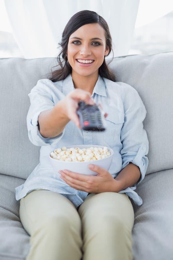 Rozochocona ładna brunetka ogląda tv i je wystrzał kukurudzy zdjęcie royalty free