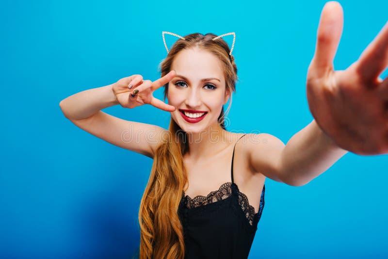 Rozochocona ładna dziewczyna z kotów ucho w diamentach na głowie pozuje kamera, brać selfie, pokazywać pokój, cieszy się przyjęci zdjęcia stock