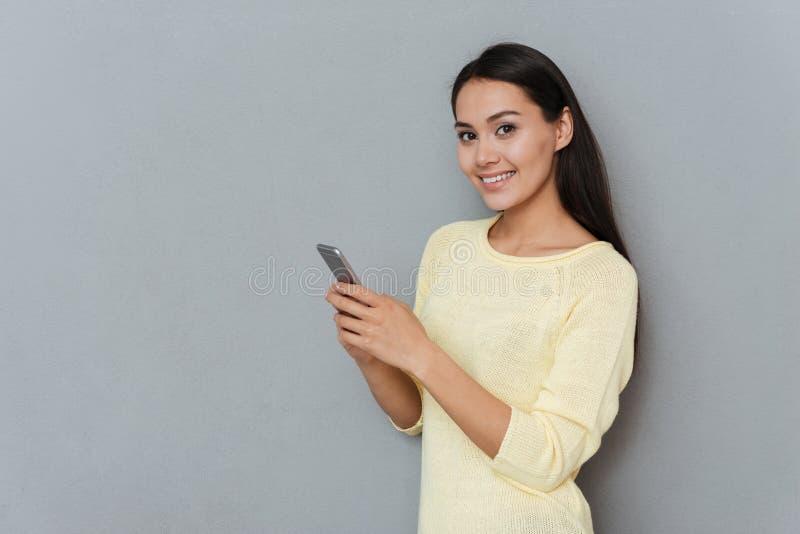 Rozochocona ładna młodej kobiety pozycja i używać telefon komórkowy zdjęcia royalty free