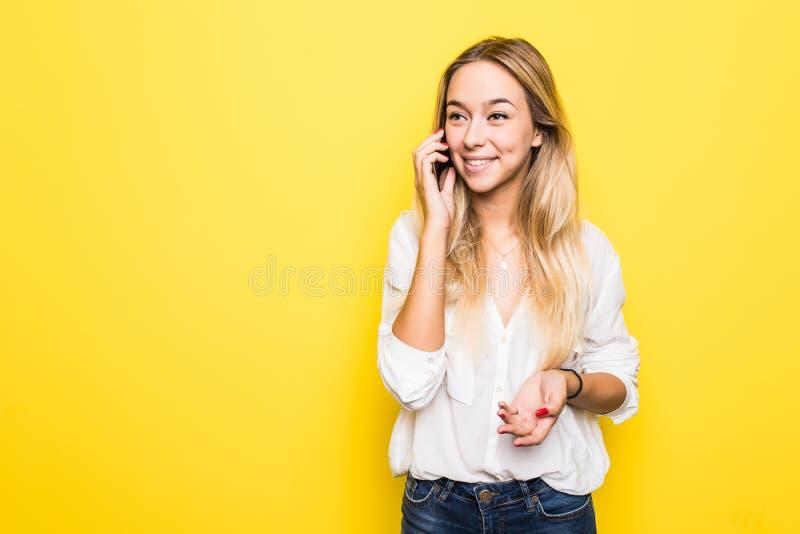 Rozochocona śliczna piękna młodej kobiety rozmowa na telefonie komórkowym odizolowywającym nad kolor żółty ściany tłem obraz stock