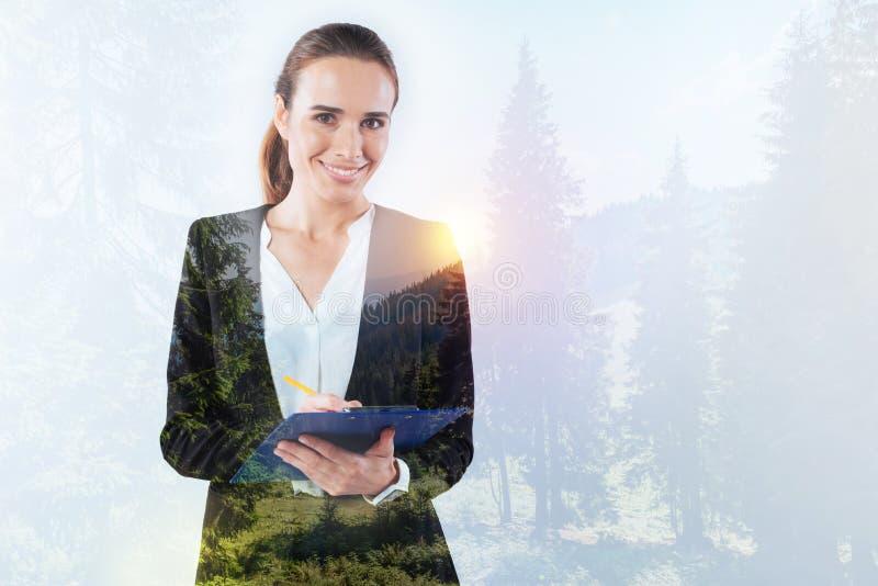 Rozochocona życzliwa kobieta z piórem i błękitną falcówką zdjęcie stock