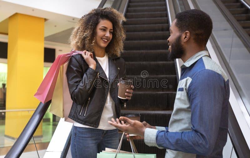Rozochocona afrykańska para miło opowiada z kawą iść obraz stock