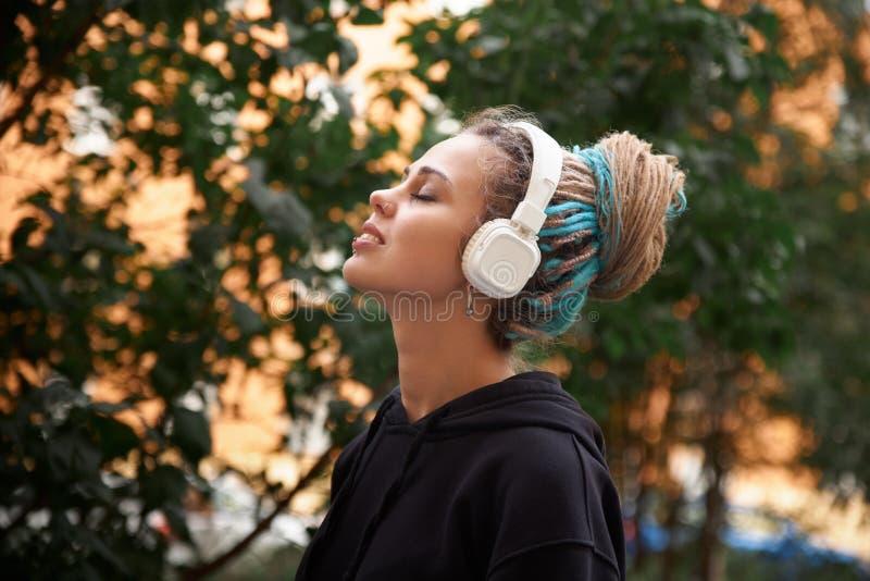 Rozochocona atrakcyjna młoda dziewczyna w hoodie i barwionych dreadlocks obrazy royalty free