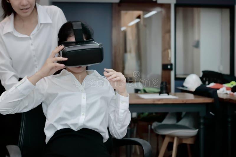 Rozochocona Azjatycka biznesowa kobieta jest ubranym rzeczywisto?? wirtualna szk?a w biurze fotografia royalty free