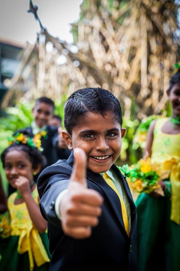 Rozochocona Azjatycka chłopiec w kostiumu pokazuje jego kciuk w górę tła inni dzieci przeciw obraz royalty free