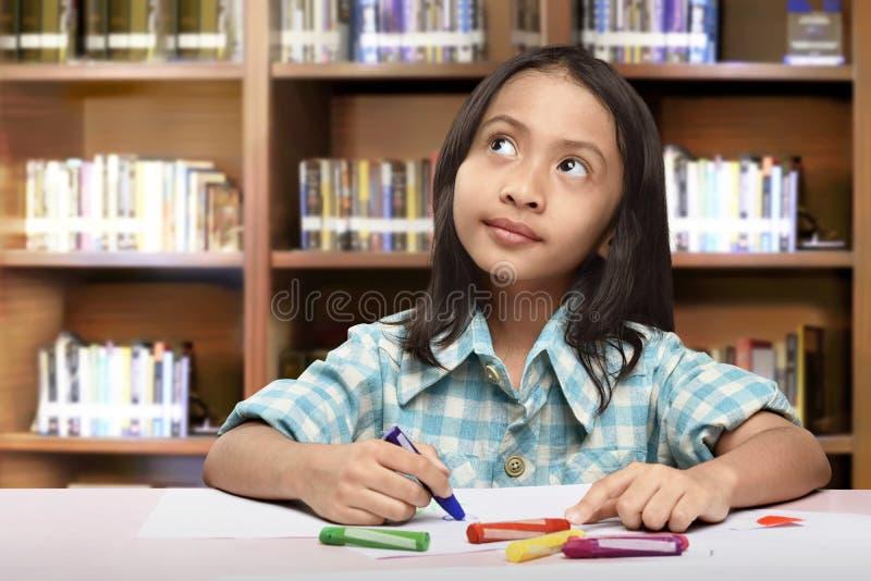 Rozochocona azjatykcia dzieciak dziewczyna z kredką chce rysować coś zdjęcia royalty free