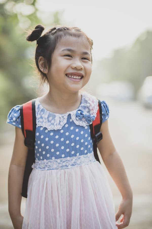 Rozochocona azjatykcia dziecko szkoły paczka na tylnej toothy uśmiechniętej twarzy obraz stock