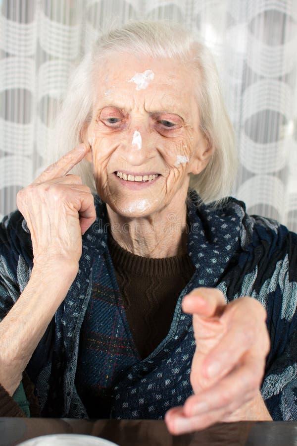 Rozochocona babcia stosuje twarzy śmietankę obraz stock
