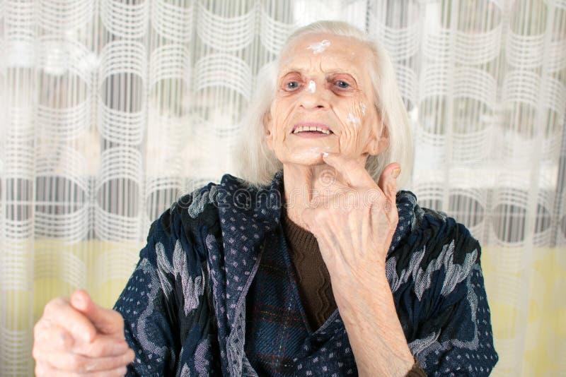 Rozochocona babcia stosuje twarzy śmietankę obraz royalty free