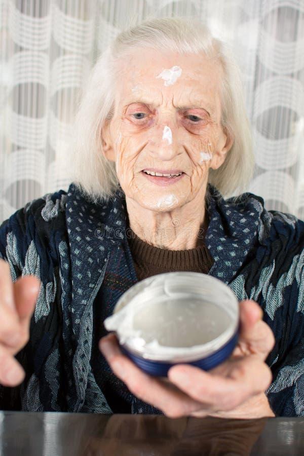 Rozochocona babcia stosuje twarzy śmietankę fotografia stock