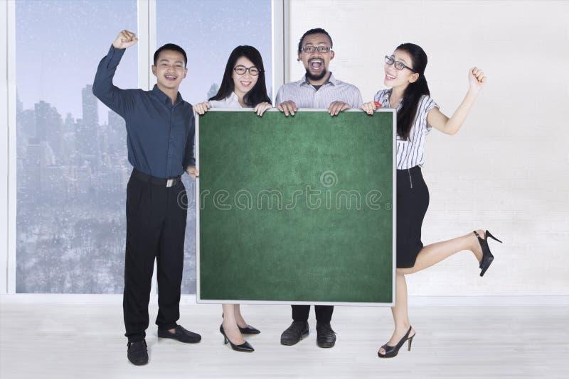 Rozochocona biznes drużyna z blackboard zdjęcie stock