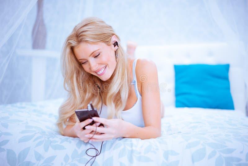 Rozochocona blond dziewczyna słucha muzyka na jej smartphone obrazy royalty free