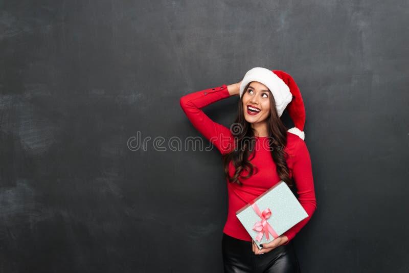 Rozochocona brunetki kobieta w czerwonej bluzce i bożych narodzeniach kapeluszowych obraz stock