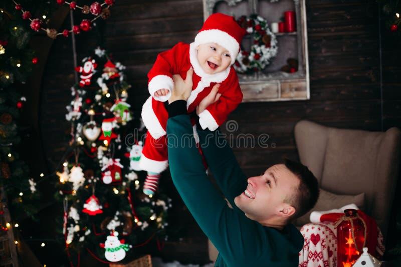 Rozochocona chłopiec śmia się i bawić się z rodzicem w bożych narodzeniach pracownianych obraz royalty free