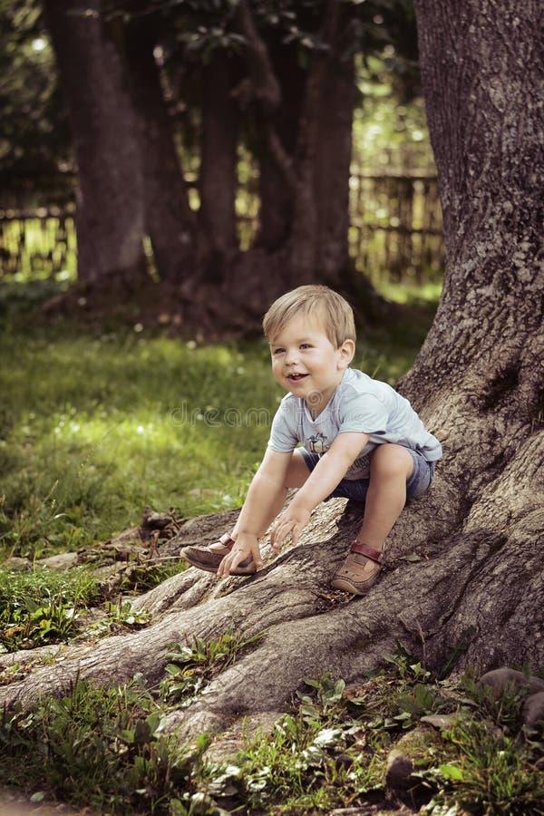 Rozochocona chłopiec bawić się w parku obraz stock