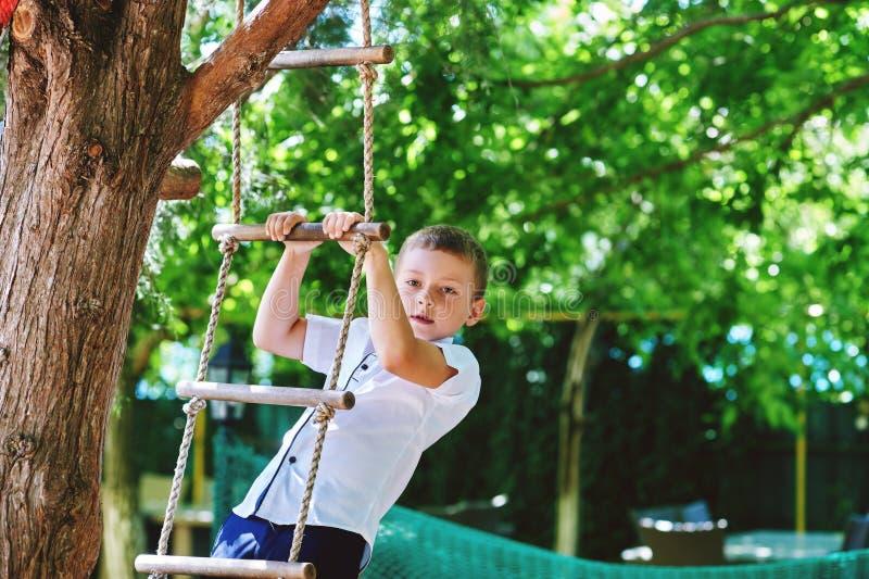 Rozochocona chłopiec bawić się w parku na linowej drabinie fotografia stock