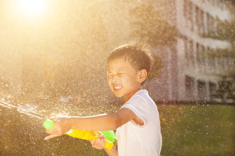 Rozochocona chłopiec bawić się wodnych pistolety w parku obraz stock