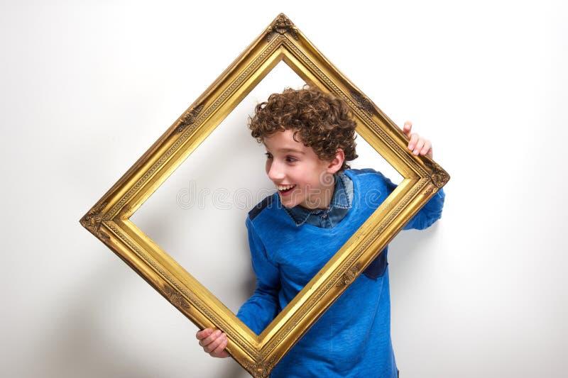 Rozochocona chłopiec mienia obrazka rama obraz royalty free