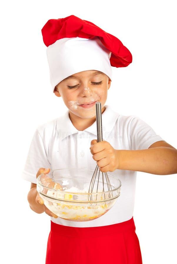 Rozochocona chłopiec miesza ciasto zdjęcia stock
