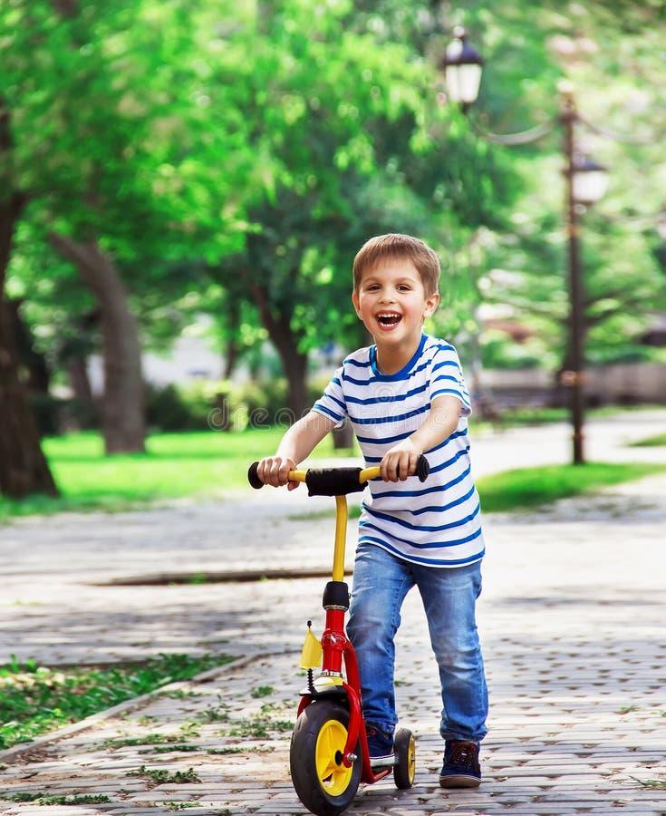 Rozochocona chłopiec na hulajnoga, bawić się w parku na tle o zdjęcia royalty free