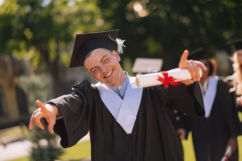 Rozochocona chłopiec pokazuje everyone w jardzie jego dyplom obrazy royalty free