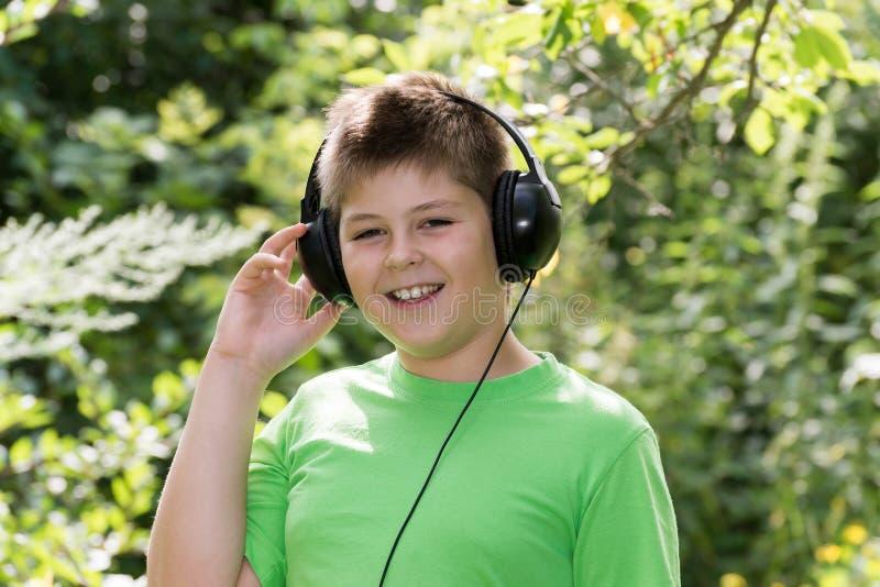 Rozochocona chłopiec słucha muzyka z hełmofonami w parku zdjęcia stock