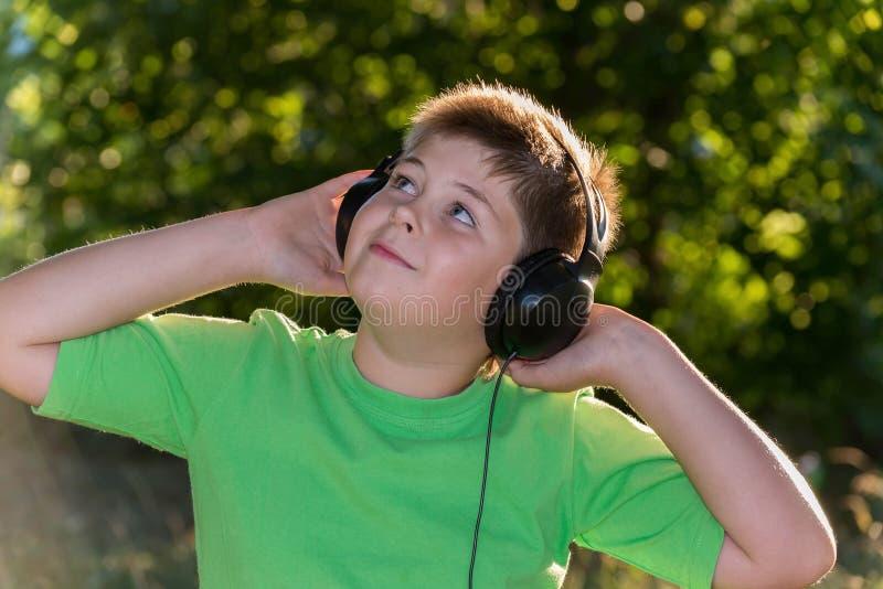 Rozochocona chłopiec słucha muzyka z hełmofonami w parku zdjęcie stock
