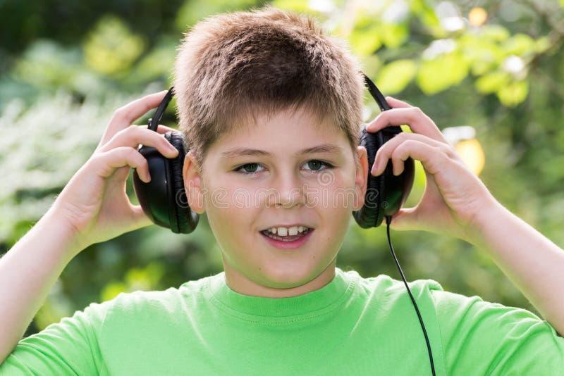 Rozochocona chłopiec słucha muzyka z hełmofonami w parku fotografia royalty free