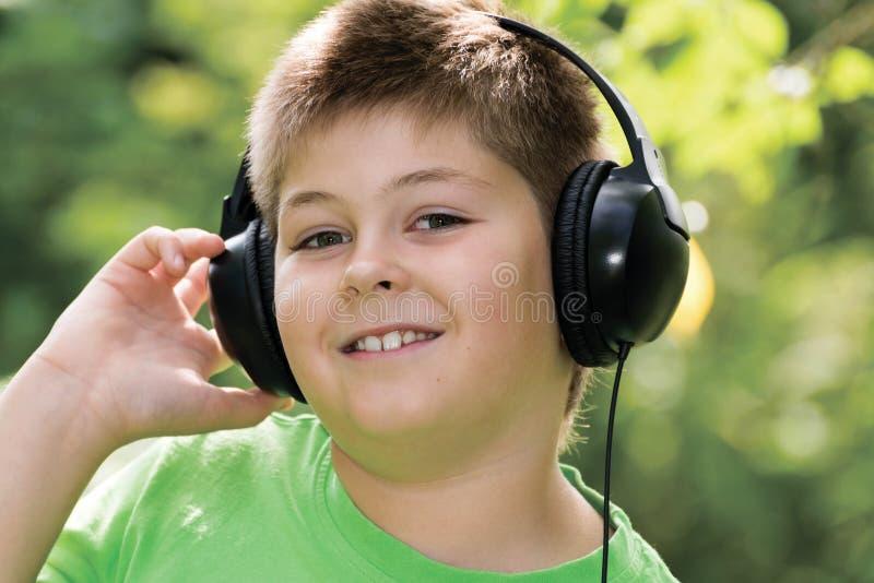 Rozochocona chłopiec słucha muzyka z hełmofonami w parku obraz royalty free