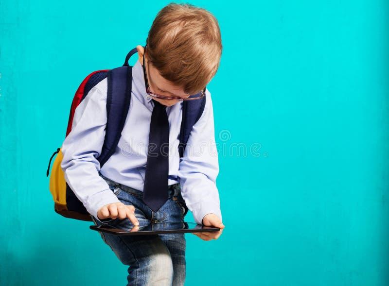 Rozochocona chłopiec trzyma cyfrową pastylki agę z dużym plecakiem zdjęcie royalty free