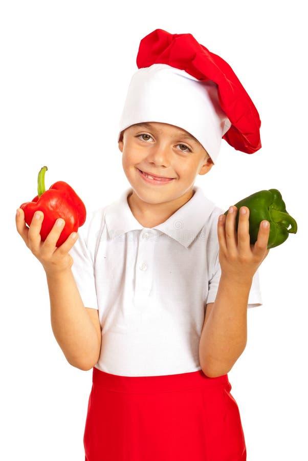 Rozochocona chłopiec trzyma dzwonkowych pieprze fotografia stock