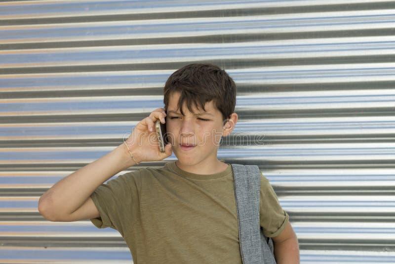 Rozochocona chłopiec używa telefon komórkowego obrazy royalty free
