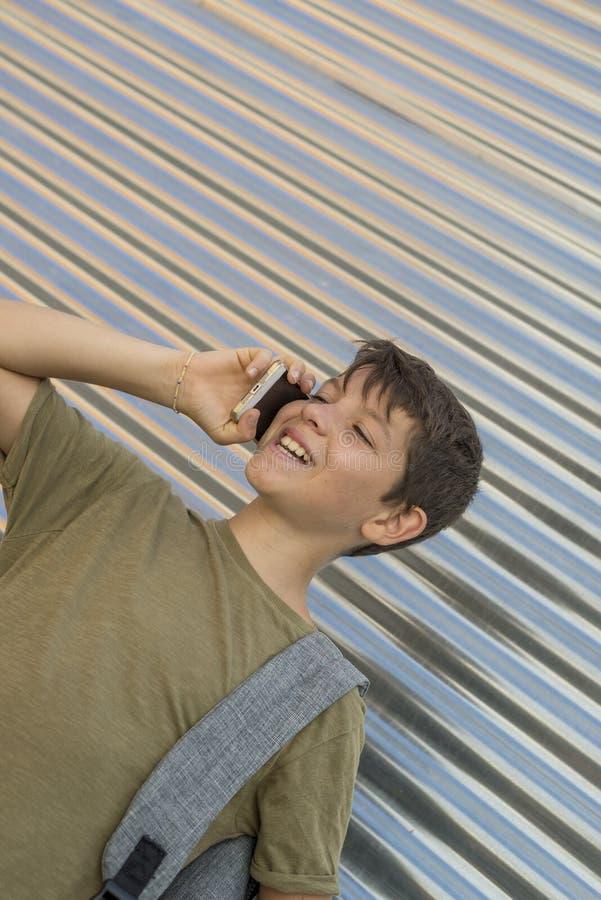 Rozochocona chłopiec używa telefon komórkowego zdjęcia stock