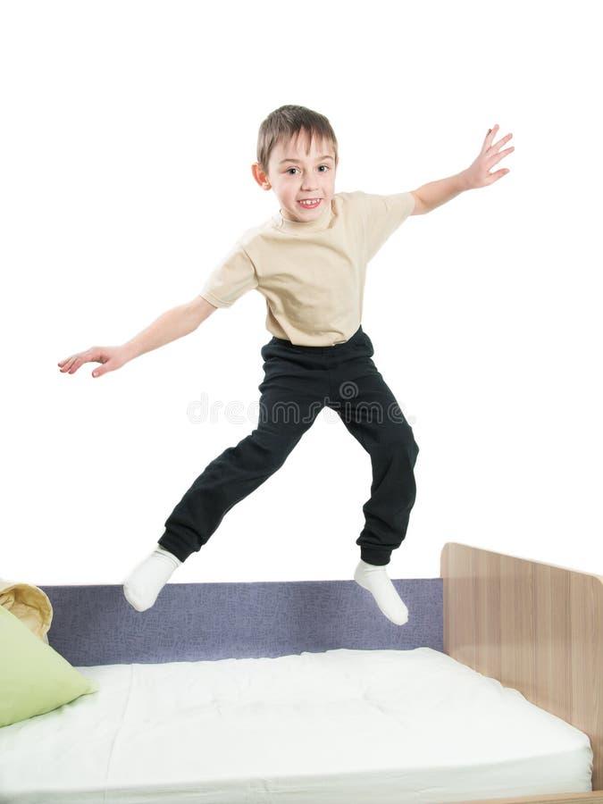 Rozochocona chłopiec w koszulowym, spodniowym doskakiwaniu na i jego ręki obrazy royalty free